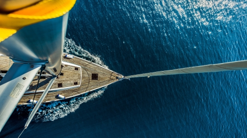 Top view of sailing boat in deep blue sea.